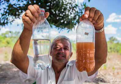 Un miembro de una comunidad de MATOPIBA muestra dos botellas de agua: una con agua limpia, la otra con agua de un río, que está sucia con sedimentos de las plantaciones de soja. El sedimento también contiene agrotóxicos, lo que hace que el agua ya no sea potable. Rosilene Miliotti/FASE